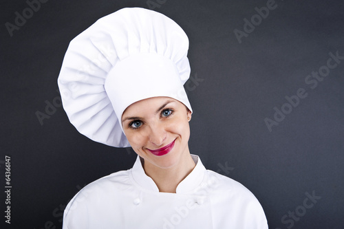 Close-up woman cook lsmiling over dark wall