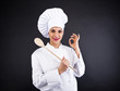 Portrait of young woman chef with spoon on dark background