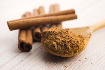 Cinnamon, whole sticks behind wooden spoon with a heap of powder