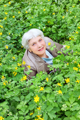 Happy beautiful elderly woman sitting on a glade of yellow flowe