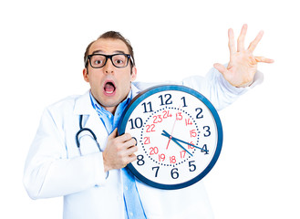 Tired, running out of time. Stressed doctor holding wall clock
