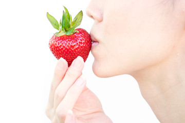Happy young woman eating mellow strawberry