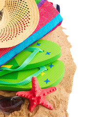 sunbathing accessories and straw hat on sand