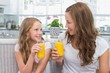 Mother and daughter with orange juice glasses in kitchen