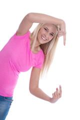 Junges blondes Mädchen zeigt auf ein Schild - isoliert in rosa