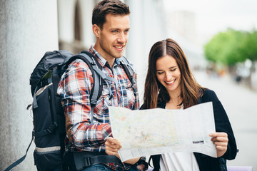 Smiling backpackers looking at city map