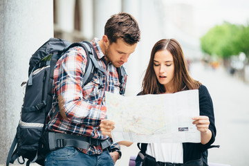 Backpackers looking at city map on street