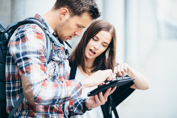 Couple of tourists looking at city map on tablet computer