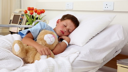 Little sick boy sleeping in bed with teddy bear