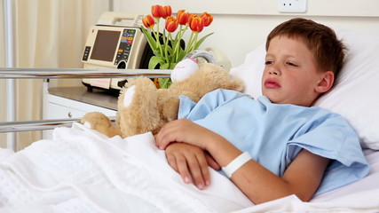 Little sick boy lying in bed with teddy bear