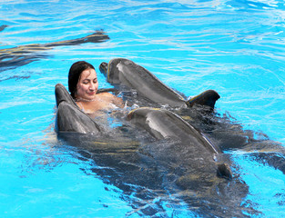 Happy beautiful young girl laughs and swims with dolphins in blu