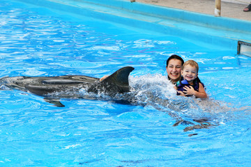 Happy beautiful young woman with a small child laughs and swims
