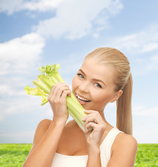 woman biting piece of celery or green salad