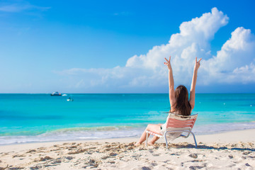 Young happy woman in a beach chair on summer vacation