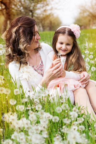 Mother and daughter in field with dandelions