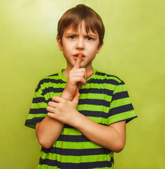 young boy kid shows sign hand gesture finger to lips mouth shh s