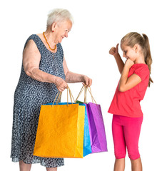 Smiling grandmother with granddaughter with shopping bags