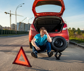 depressed man sitting near car with punctured tire