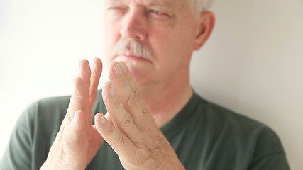 older man taps fingers together