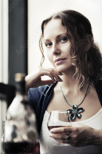 Sad beautiful woman drinking cognac at restaurant