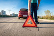 man placing red triangle sing on road after car crash