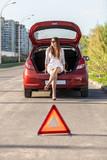 helpless woman sitting near broken red car poster