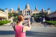 Young woman taking picture of Catalan Art Museum (MNAC).