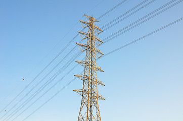 High voltage poles on blue sky background