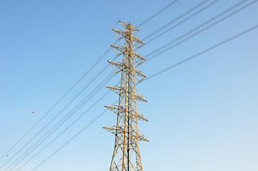 High voltage poles on blue sky background