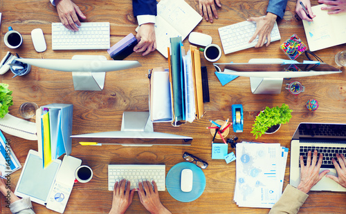 Group of Business People Working on an Office Desk - 64385748