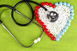 Heart of pills and stethoscope on wooden background