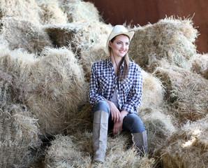 Beautiful cowgirl style model posing on farmland in hay