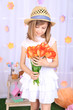 Beautiful small girl holding flowers on decorative background