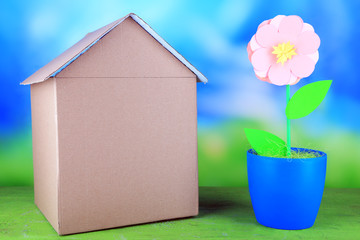 Cardboard house with flower in pot on table on bright