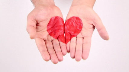 Male and female hands gather and show red heart