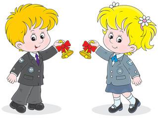Schoolgirl and schoolboy ringing the bells