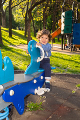 Toddler boy in seesaw in a sunny day