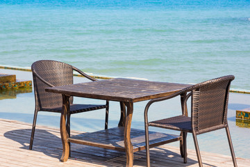 Table chair beside sea
