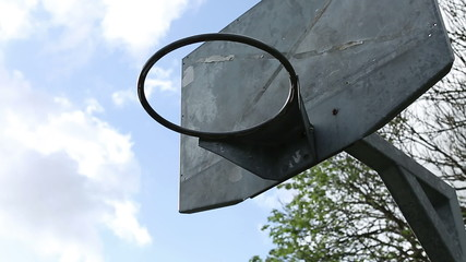 Sliding shot of a basketball hoop in the summer breeze