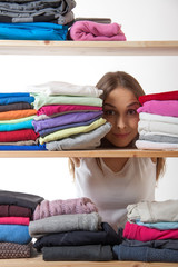 young woman hiding behind a shelf with clothing