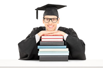 College graduate posing behind a stack of books