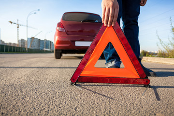 photo of man putting triangle warning sign on road