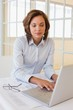 Businesswoman working on blueprints and laptop in office