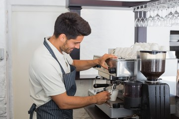 Waiter making cup of coffee at coffee shop