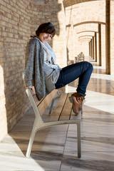 Beautiful caucasian woman posing on a bench