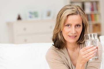 attraktive ältere frau mit einem glas wasser
