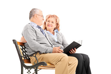 Mature couple sitting on a bench and reading book