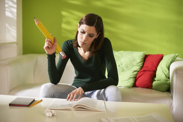 female student doing homeworks with big pencil