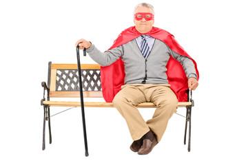 Senior in superhero costume sitting on a bench
