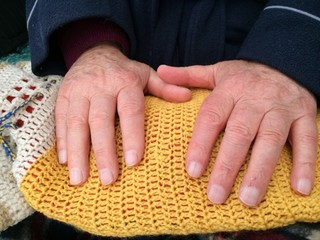 old man hands on a warm bag